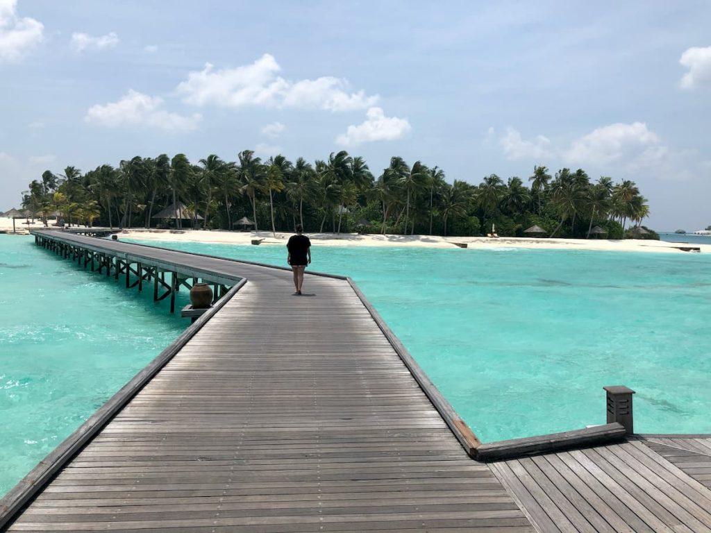 spa-maldives-woman-walking-walkway-ocean
